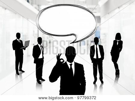 Silhouettes of business people with speech bubble on office background