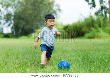 Little boy play soccer at outdoor