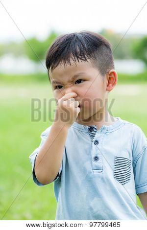 Asian little kid feeling itchy on his nose