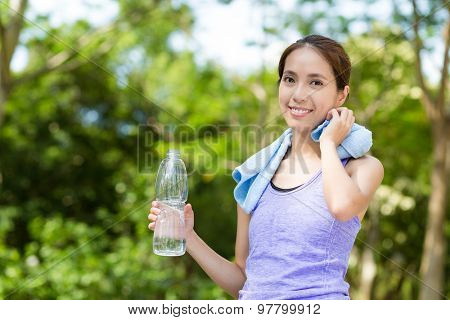 Woman hold with water bottle at outdoor after doing exercise