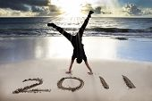stock photo of new years  - happy new year 2011 on the beach of sunrise  - JPG