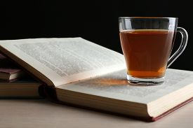 foto of black tea  - Glass cup of tea with book on wooden table on black background - JPG