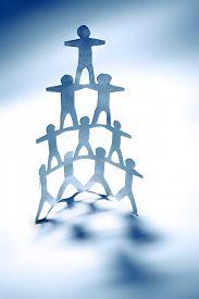 stock photo of human pyramid  - Human team pyramid holding hands - JPG