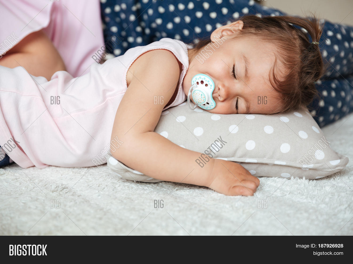 Little girl nipple Photo of pretty little girl child indoors with nipple sleeping on bed near  mother. Eyes