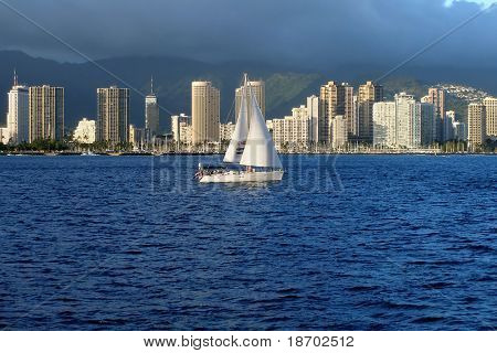 Boat sailing along Honolulu skyscrapers in Hawaii