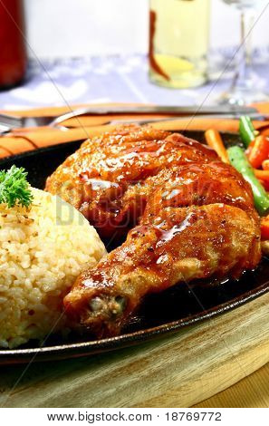 chicken leg with rice served on a hot sizzling plate
