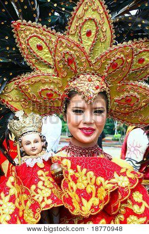 menina filipina em traje carregando uma imagem do menino Jesus