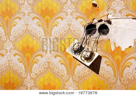 Old wallpaper with loose power socket