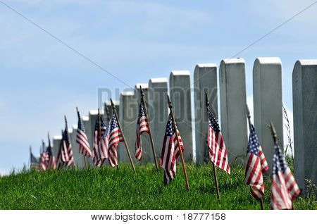 Gravestones decorated with U.S. flags to commemorate Memorial Day at the Arlington National Cemetery in Arlington, Virginia, near Washington DC. Narrow DOF.