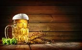 Oktoberfest beer with wheat  and hops on wooden table poster