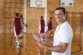 Portrait of basketball coach holding clipboard in the court poster