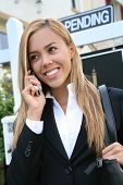 picture of real-estate agent  - A beautiful young real estate agent woman on the phone - JPG