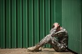 Frustrated military soldier sitting with hands on head in boot camp poster