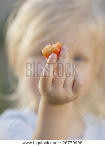 Toddler Eating A Tomato