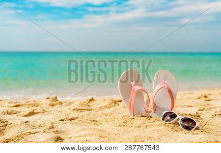 poster of Pink And White Sandals, Sunglasses On Sand Beach At Seaside. Casual Fashion Style Flipflop And Glass
