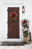 stock photo of winterberry  - An antique door decorated for Christmas with freshly fallen snow outside - JPG
