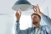Man Changing Light Bulb In Pendant Lamp Indoors poster