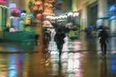 Abstract Background Of Blurred People Under Umbrellas Hurrying Down The City Street In Rainy Evening poster