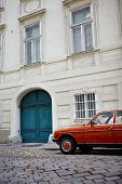 Retro Orange Car On Pavement Near The Old White Building. Cyan Door poster