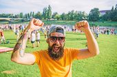 Cheerful Fan At Summer Fest. Man Bearded Hipster In Front Of Crowd People Raise Fists Green Riversid poster