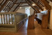 stock photo of pews  - the upstairs of a very small church with a beamed ceiling and pews - JPG