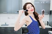A portrait of an attractive young woman in a dark blue dress with white dots doing make-up in the ki poster