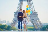 Romantic Couple Together In Paris With Bunch Of Colorful Balloons Looking At The Eiffel Tower poster
