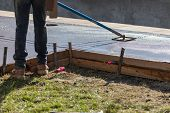 Construction Worker Smoothing Wet Cement With Long Handled Edger Tool poster