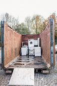 Old electrical appliances like tv sets and washing machines in container of recycling center  poster