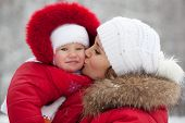 picture of ruddy-faced  - Young mother with her baby daughter in their red jackets - JPG