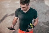 A Male Athlete Holds Phone In His Hand, Launches An Application For Workout. In Summer, View From To poster