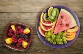 Sliced Fruit On A Wooden Background. Sliced Fruit On A Plate poster