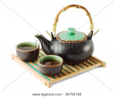 Brown Teapot And Teacups On The Wooden Trivet