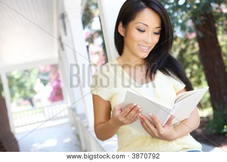 Pretty Asian Woman Reading At Home