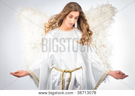 Woman in angel costume with artificial feather wings isolated on white background spirituality purity dreams religion