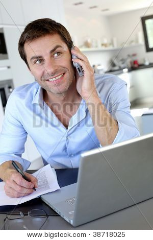 Home office worker talking on mobile phone