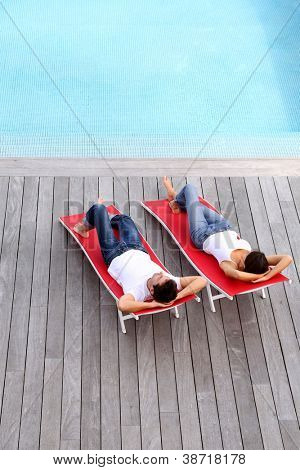 Couple relaxing in long chairs by outdoor pool