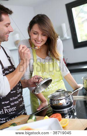 Man preparing dinner and making her wife taste the food