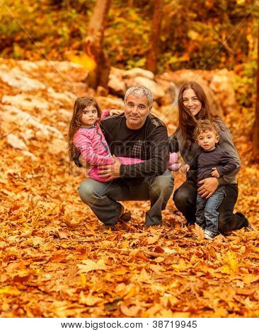 Photo of young happy family in autumnal forest, portrait of friendly family sitting on dry autumn foliage in park, parents with two adorable children having fun outdoors, love concept