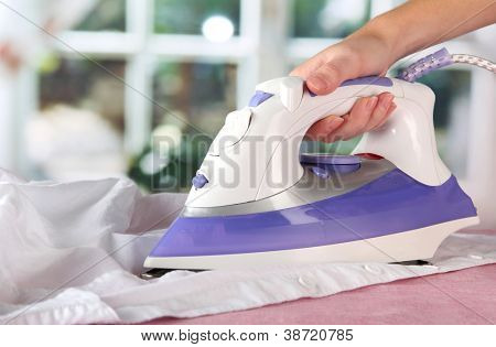 Woman hand ironing a shirt, on window background
