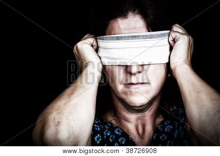 Grunge image of a serious woman with a handkerchief covering her eyes to avoid seeing isolated on black (useful to illustrate gender discrimination or prejudices)