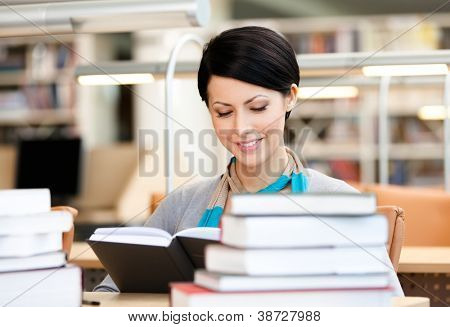 Woman surrounded with piles of books reads sitting at the desk at the library. Training process