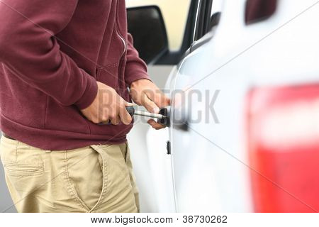 View down the length of a car to a man committting a car break in and theft with a screw driver inserted into the lock