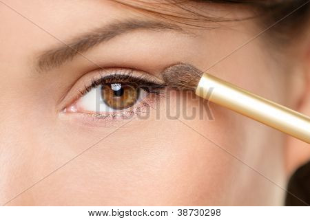 Eye makeup woman applying eyeshadow powder. Woman putting shadow powder on eyes with makeup brush. Closeup of eyelid and eyebrow.