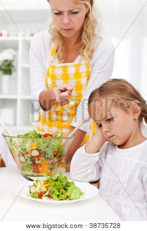 Eat your veggies right now - mother pointing her child in the right direction