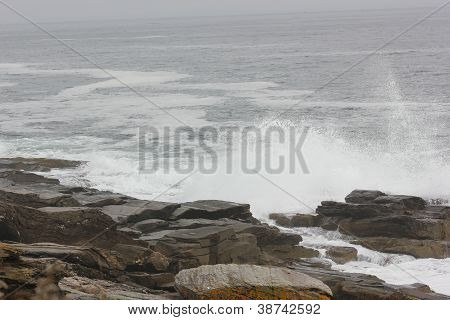 Waves and tide pool along rocky coast of Maine at Two Lights State Park