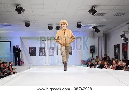 MOSCOW - NOVEMBER 4: Man in jacket and viewers in fashion house of Slava Zaitsev on November 4, 2011 in Moscow, Russia.