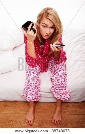 Joven descontenta en su pijama sentado en el borde de la cama, cambiando los canales de TV