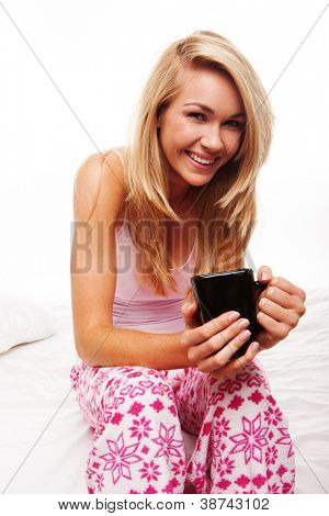 Smiling blonde woman sittting on the edge of her bed in pyjamas drinking a mug of morning coffee
