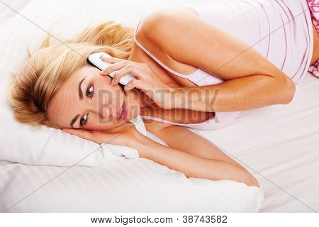 Pretty blonde woman lying in her bed listening to a conversation on her mobile with wide open eyes